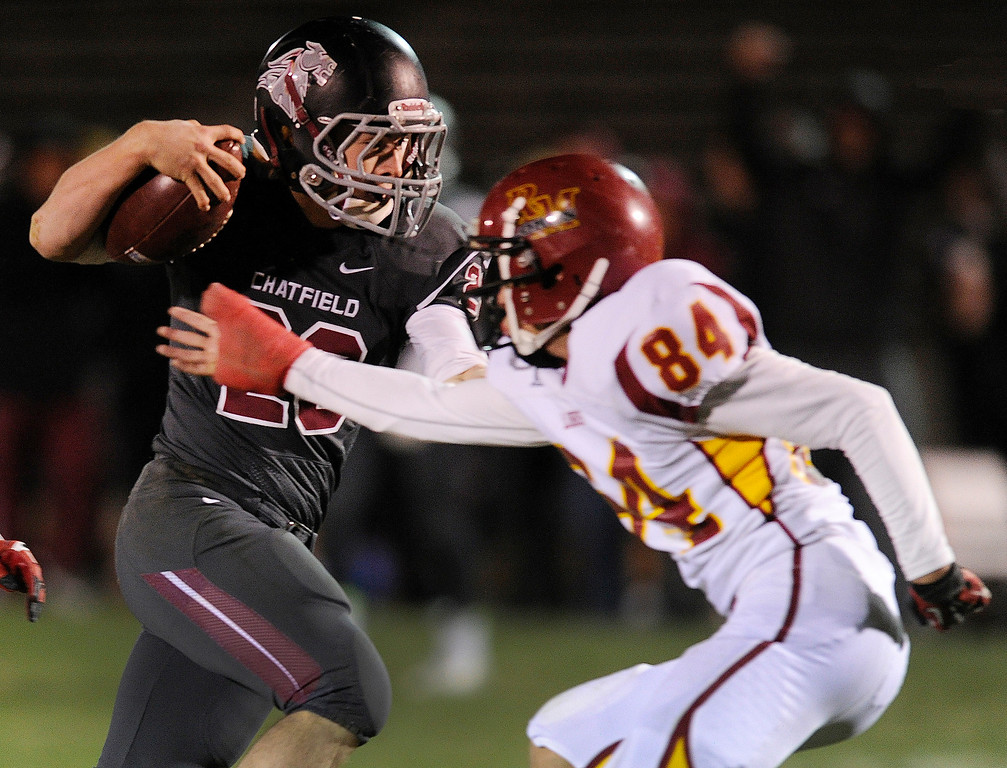 . Chatfield running back Michael Callahan-Harris (23) made a move past Lobos defensive back Jordan Williams (84) on a touchdown run in the second half. The Chatfield High School football team defeated Rocky Mountain 35-12 at Jefferson County Stadium Thursday night, October 31, 2013. Photo By Karl Gehring/The Denver Post