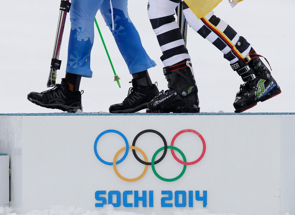 . Women\'s giant slalom gold medal winner Slovenia\'s Tina Maze, left and bronze medal winner, Germany\'s Viktoria Rebensburg, leave the podium after a flower ceremony at the Sochi 2014 Winter Olympics, Tuesday, Feb. 18, 2014, in Krasnaya Polyana, Russia. (AP Photo/Gero Breloer)