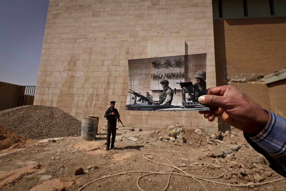 . Iraqi policeman Ahmed Naji stands on the grounds of the Iraqi National Museum at the site of a photograph of U.S. soldiers on guard outside the museum taken by Associated Press photographer Anja Niedringhaus on Nov. 11, 2003. Tens of thousands of artifacts chronicling some 7,000 years of civilization in Mesopotamia are believed to have been looted from Iraq in the chaos which followed the the U.S.-led invasion in 2003. Despite international efforts to track items down, fewer than half of the artifacts have so far been retrieved. Photo taken on March 13, 2013. (AP Photo/Maya Alleruzzo)
