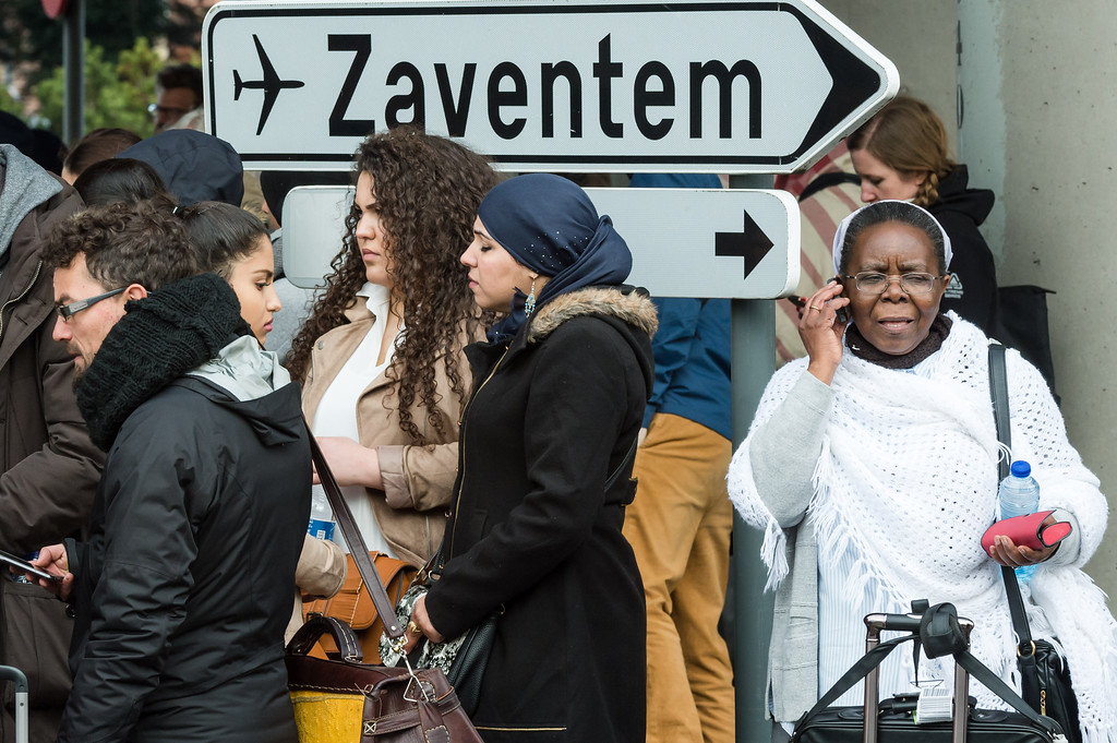 . People stand near Brussels airport after being evacuated following  explosions that rocked the facility in Brussels, Belgium, Tuesday March 22, 2016. Authorities locked down the Belgian capital on Tuesday after explosions rocked the Brussels airport and subway system, killing  a number of people and injuring many more. Belgium raised its terror alert to its highest level, diverting arriving planes and trains and ordering people to stay where they were. Airports across Europe tightened security. (AP Photo/Geert Vanden Wijngaert)