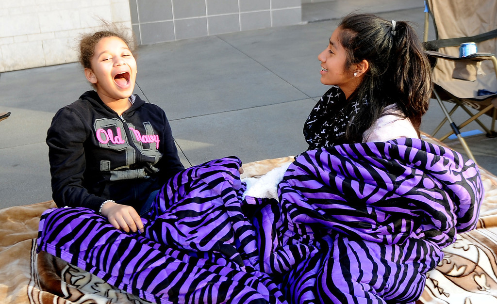 . Eleven-old Dejae Elias, left, of Pasadena shares a laugh with thirteen year-old Monse Elias of San Francisco as they camp out for the Rose Parade along Colorado Boulevard in Pasadena, Calif., on Tuesday, Dec. 29, 2013.     (Keith Birmingham Pasadena Star-News)
