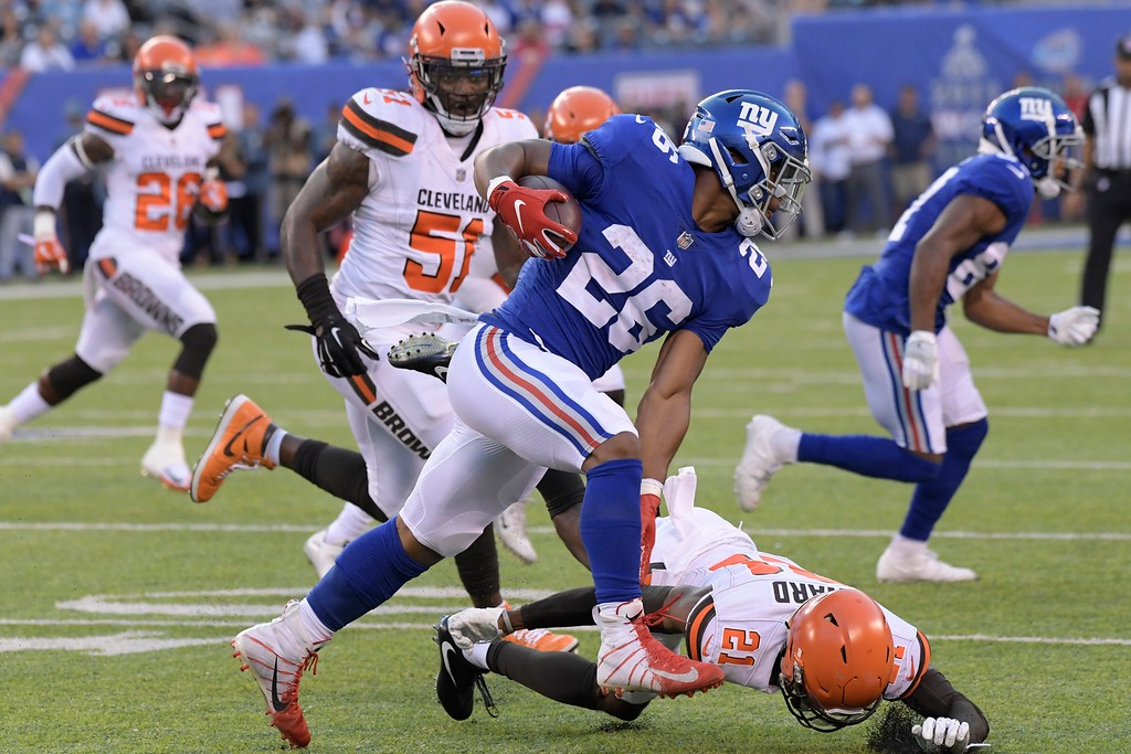 . New York Giants running back Saquon Barkley (26) rushes past Cleveland Browns\' Denzel Ward (21) during the first half of a preseason NFL football game Thursday, Aug. 9, 2018, in East Rutherford, N.J. (AP Photo/Bill Kostroun)