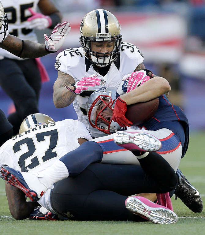 . New Orleans Saints safeties Malcolm Jenkins (27) and Kenny Vaccaro (32) tackle New England Patriots wide receiver Julian Edelman, right, in the first quarter of an NFL football game Sunday, Oct.13, 2013, in Foxborough, Mass. (AP Photo/Steven Senne)