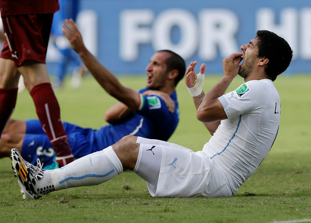. Uruguay\'s Luis Suarez holds his teeth after running into Italy\'s Giorgio Chiellini\'s shoulder during the group D World Cup soccer match between Italy and Uruguay at the Arena das Dunas in Natal, Brazil, Tuesday, June 24, 2014. (AP Photo/Ricardo Mazalan)