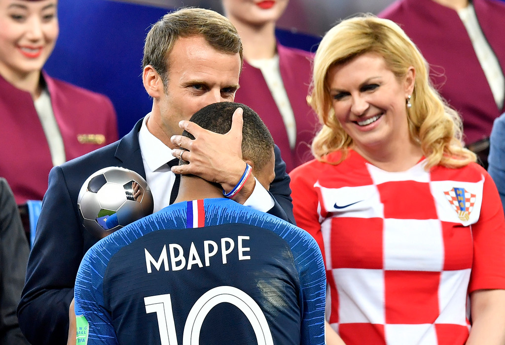 . Croatian President Kolinda Grabar-Kitarovic, right, looks on as French President Emmanuel Macron kisses France\'s Kylian Mbappe after France won the final match between France and Croatia at the 2018 soccer World Cup in the Luzhniki Stadium in Moscow, Russia, Sunday, July 15, 2018. (AP Photo/Martin Meissner)