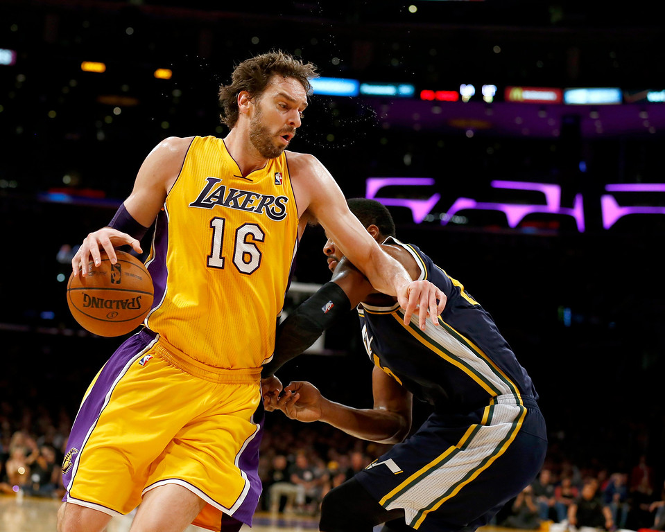 . epa04007680 Los Angeles Lakers Pau Gasol of Spain (L) spins away from Utah Jazz defender Derrick Favors (R) in the first half action of their NBA game at Staples Center in Los Angeles, California USA, 03 January 2014.  EPA/PAUL BUCK CORBIS OUT