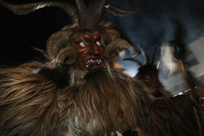 . Members of the Haiminger Krampusgruppe dressed as the Krampus creature parade on the town square during their annual Krampus night in Tyrol on December 1, 2013 in Haiming, Austria. Krampus, in Tyrol also called Tuifl, is a demon-like creature represented by a fearsome, hand-carved wooden mask with animal horns, a suit made from sheep or goat skin and large cow bells attached to the waist that the wearer rings by running or shaking his hips up and down. Krampus has been a part of Central European, alpine folklore going back at least a millennium, and since the 17th-century Krampus traditionally accompanies St. Nicholas and angels on the evening of December 5 to visit households to reward children that have been good while reprimanding those who have not. However, in the last few decades Tyrol in particular has seen the founding of numerous village Krampus associations with up to 100 members each and who parade without St. Nicholas at Krampus events throughout November and early December.  (Photo by Sean Gallup/Getty Images)
