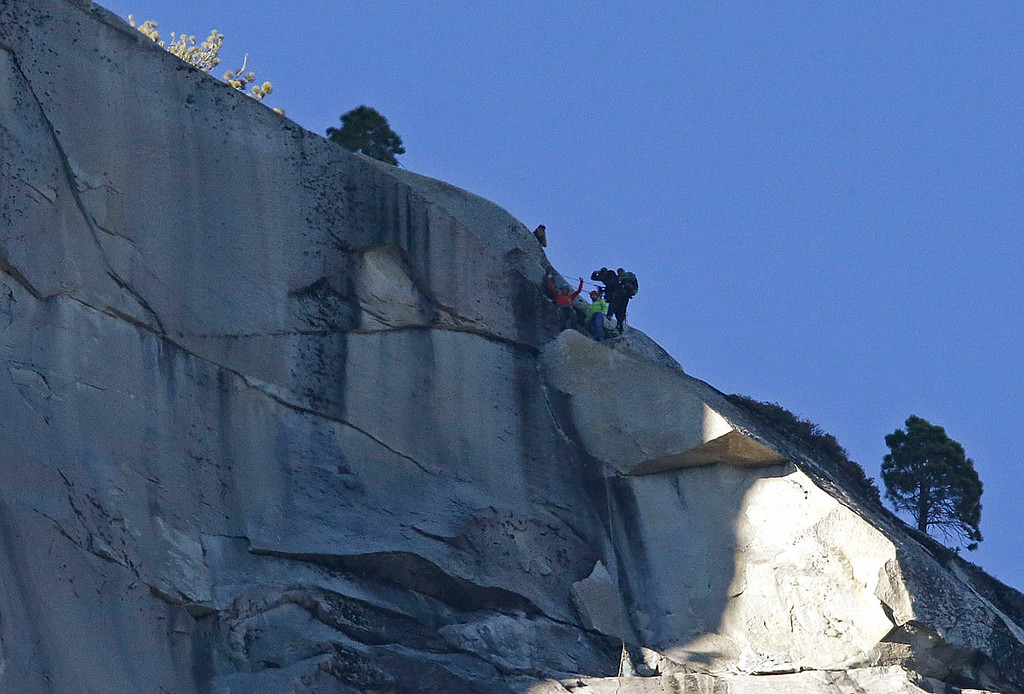 . Kevin Jorgeson, bottom left, raises his arms beside Tommy Caldwell after both reached the summit of El Capitan, Wednesday, Jan. 14, 2015, as seen from the valley floor in Yosemite National Park, Calif. Caldwell and Jorgeson became the first to free-climb the rock formation\'s Dawn Wall. They used ropes and safety harnesses to catch them in case of a fall, but relied entirely on their own strength and dexterity to ascend by grasping cracks as thin as razor blades and as small as dimes. (AP Photo/Ben Margot)