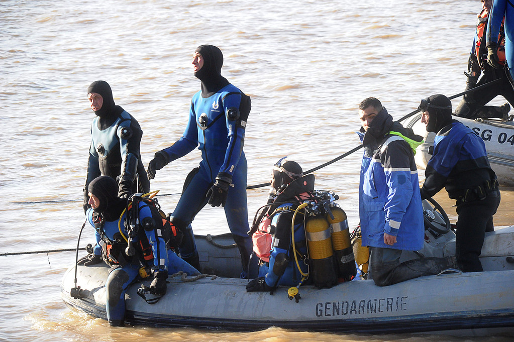 . Gendarmes take part on December 23, 2013  in Lugon-et-l\'Ile-du-Carnay, southwestern France, in an operation to lift a helicopter from the Dordogne river bed for clues into a crash that is thought to have killed a Chinese tycoon and a French winemaker.  AFP PHOTO / MEHDI FEDOUACH