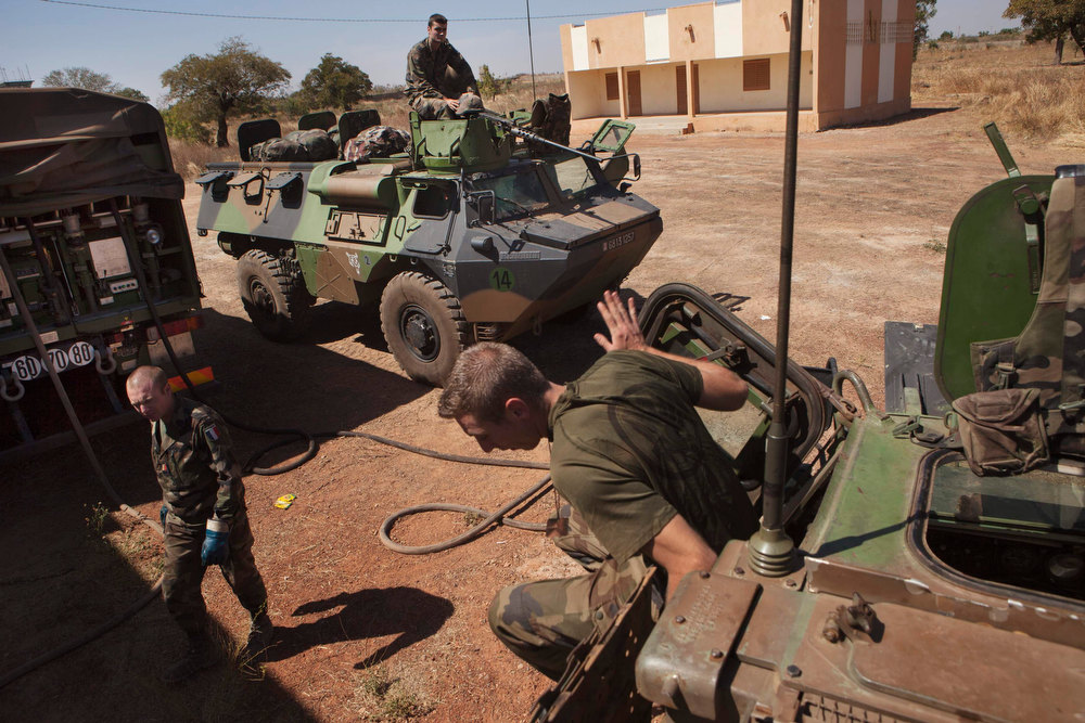 Description of . French soldiers refuel Armoured Personnel Carriers that were driven from Ivory Coast, at a Malian air base in Bamako January 15, 2013. The French army sent some 50 armoured vehicles to Mali from their military base in Ivory Coast, which arrived late Monday night. France hit Islamist rebels in Mali with fresh air strikes and deployed armoured cars on Tuesday, stepping up its intervention in the West African state as regional allies struggled to accelerate their plans to send in troops.     REUTERS/Joe Penney