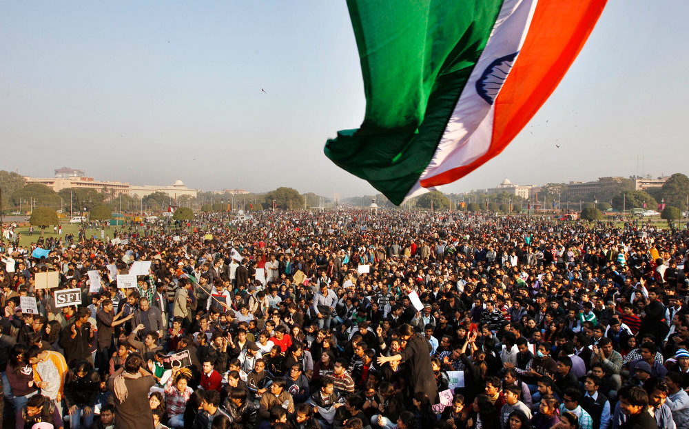 Description of . Indian flag is seen as protesters gather near the Presidential Palace during a protest in New Delhi, India, Saturday, Dec. 22, 2012.  Police in India's capital used tear gas and water cannons Saturday to push back thousands of people who tried to march to the presidential mansion to protest the recent gang rape and brutal beating of a 23-year-old student on a moving bus. (AP Photo/Tsering Topgyal)