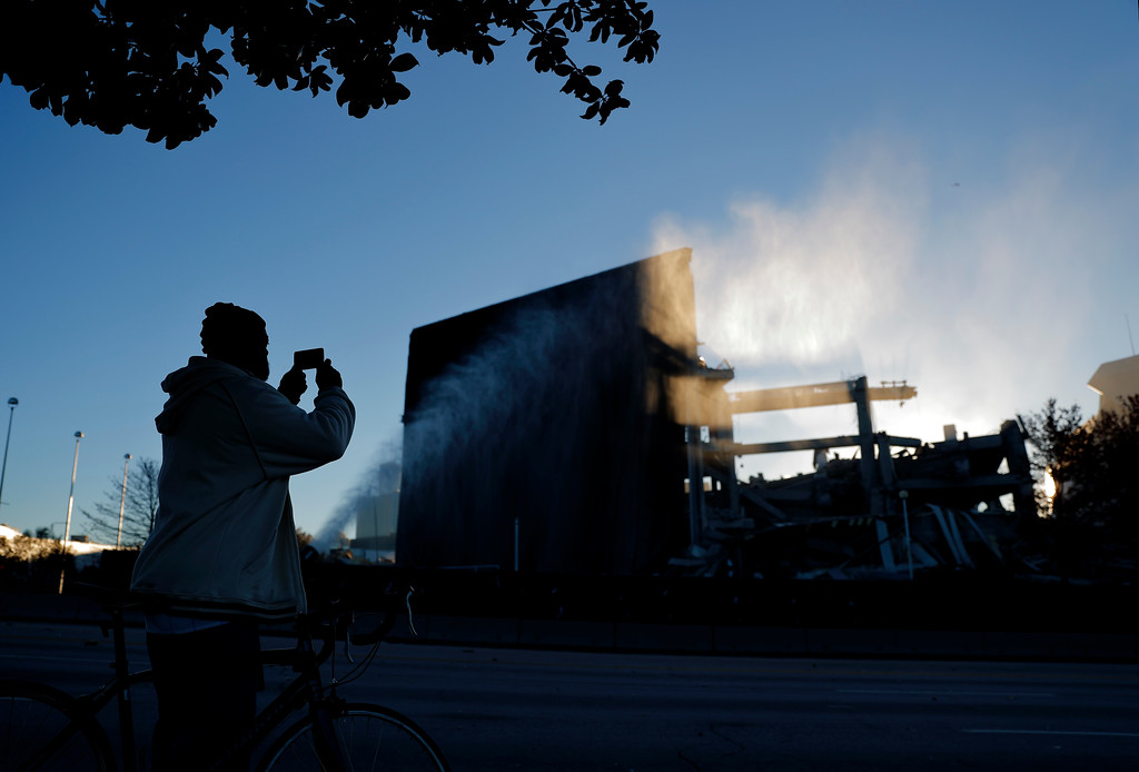 . Larry Jenkins takes a photo of the remains of the Georgia Dome after it was imploded in Atlanta, Monday, Nov. 20, 2017. The dome was not only the former home of the Atlanta Falcons but also the site of two Super Bowls, 1996 Olympics Games events and NCAA basketball tournaments among other major events. (AP Photo/David Goldman)