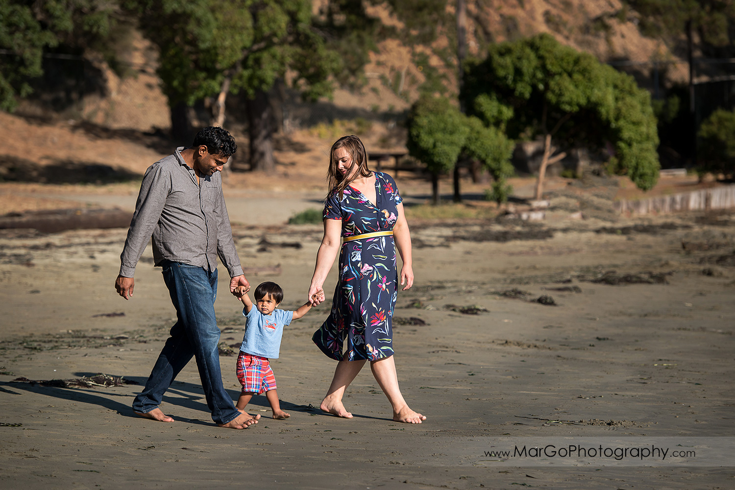 woman in blue dress with pink flowers, man in grey shirt and little boy in blue shirt and red shorts walking on the sand at Richmond Keller Beach