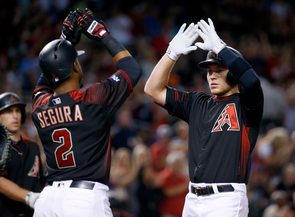 . Arizona Diamondbacks\' Brandon Drury high fives teammate Jean Segura (2) after hitting a two run home run against the Colorado Rockies during the sixth inning of a baseball game, Saturday, April 30, 2016, in Phoenix. (AP Photo/Matt York)