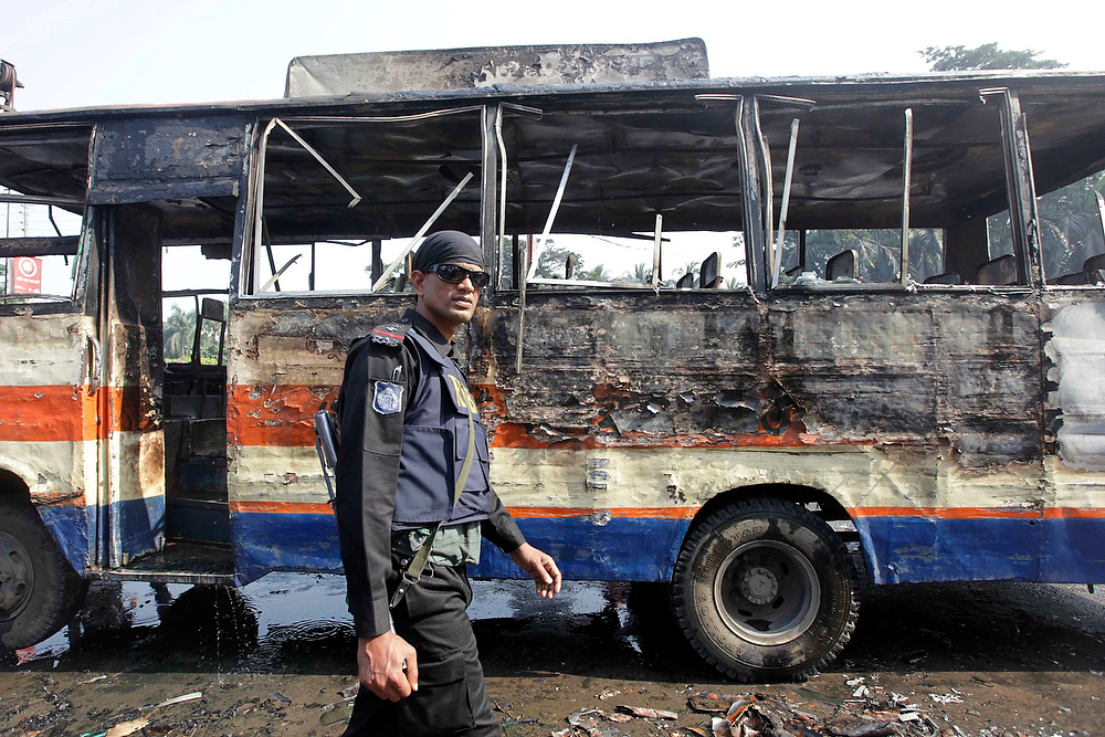 . A member of the Rapid Action Battalion inspects a burnt bus after activists of Bangladesh\'s Jamaat-e-Islami party set fire to it during a strike in Dhaka on December 4, 2012. About 100 Jamaat-e-Islami activists were arrested and 25 injured during a day-long strike by the largest Islamic party in the country on Tuesday as a part of their continuing protest for the release of their senior leaders who are facing trial against war crimes and crimes against humanity, local media reported. REUTERS/Andrew Biraj