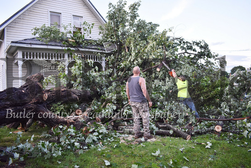 Parker resident Mike Bucholz uses a chainsaw to cut limbs off the massive tree that fell on top of his Washington Street home Sunday afternoon while his friend, Judd Jack, helps clear debris. Residents report they saw a funnel cloud touch down during the storm that damaged several homes and businesses and downed dozens of tree.