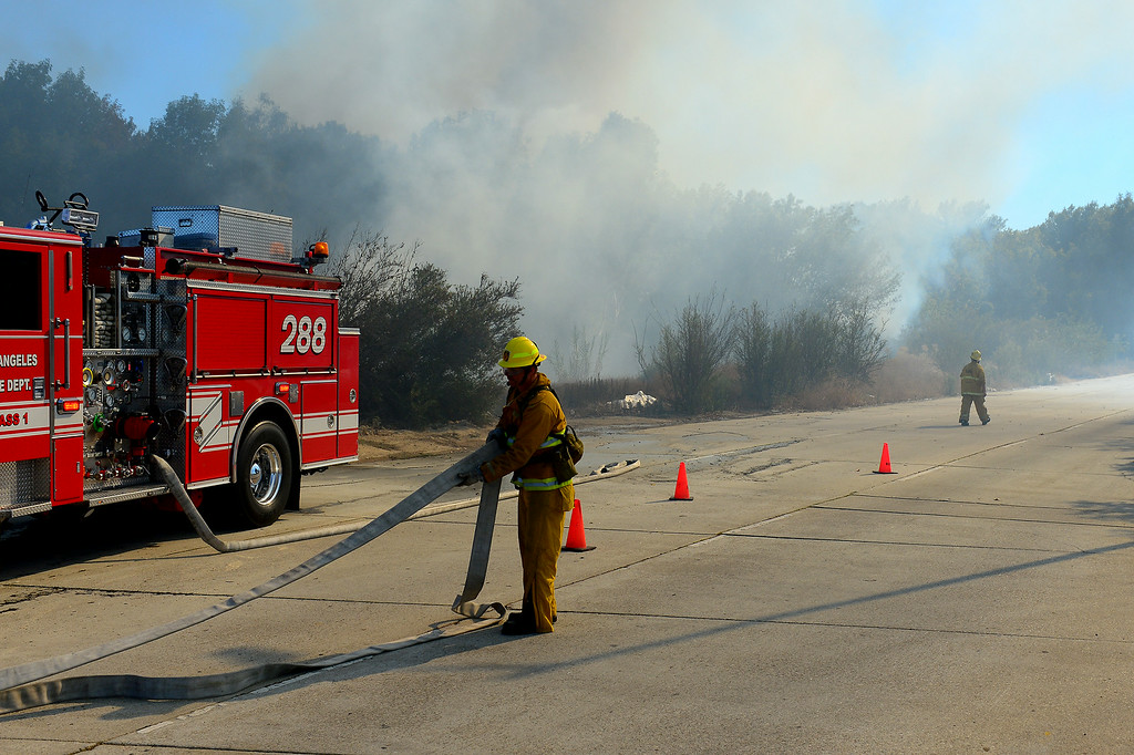 . LAFD readies fire hoses along Burbank Boulevard as a brushfire burns in the Sepúlveda Basin, Friday, August 22, 2014. (Photo by Michael Owen Baker/Los Angeles Daily News)