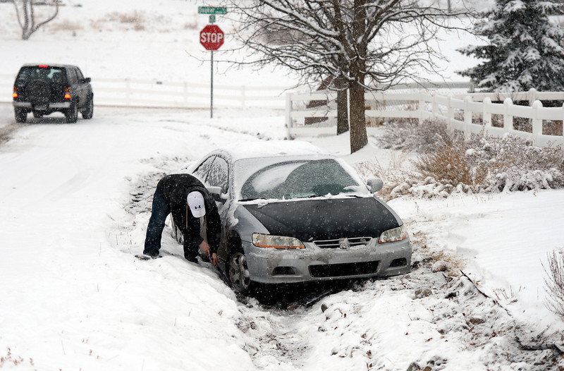 . Chris Hendren tries to use his window scraper to dig out his car, February, 21, 2013, after sliding off the road into someones yard in west Arvada. The metro area was slowed by overnight snow, roads are snow packed, icy, and lane recognition is a problem along some stretches. (Photo By RJ Sangosti/The Denver Post)