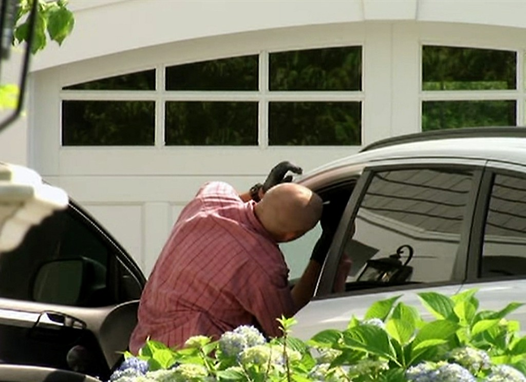 . In this image taken from video, police search a car outside the home of New England Patriots football player Aaron Hernandez, Saturday, June 22, 2013, in North Attleboro, Mass. State police officers and dogs searched Hernandez\'s home as they investigate the killing of Odin Lloyd, a semi-pro football player whose body was found nearby. (AP Photo/ESPN)