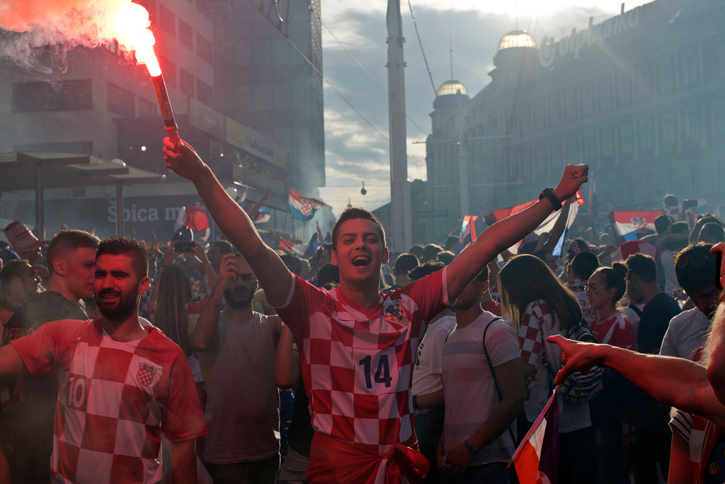 . A supporter of the Croatian national soccer team lights a flare in central Zagreb, Croatia, Sunday, July 15, 2018. Croatia\'s national soccer team lost to France in the World Cup final in Russia. (AP Photo/Marko Drobnjakovic)