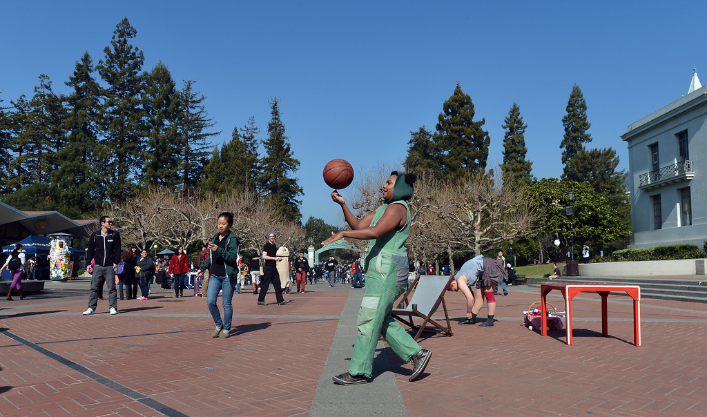 """. Circus Oz performer Ghenoa Gela warms up with a basketball as the Australian circus group entertains on Sproul Plaza at the University of California to preview their new show \""""From the Ground Up\"""" in Berkeley, Calif. on Wednesday, Feb. 13, 2013. (Kristopher Skinner/Staff)"""