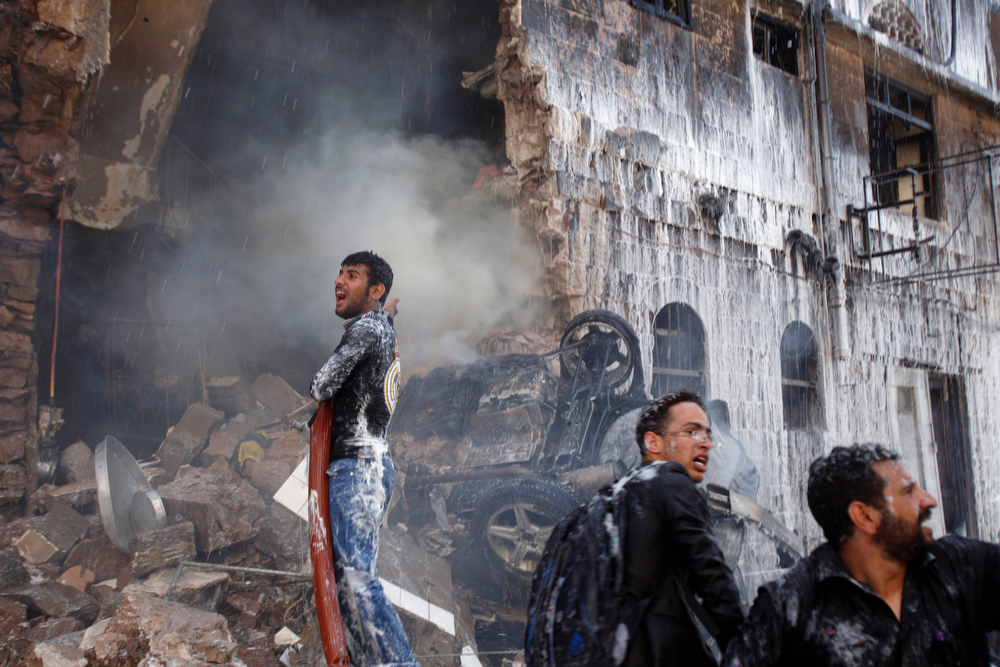 Description of . A firefighter reacts as he works at extinguishing a fire at the site of a military aircraft crash in Sanaa February 19, 2013.  A Yemeni air force plane crashed in the centre of the capital Sanaa on Tuesday, killing at least 11 people and wounding 15, security sources said. REUTERS/Khaled Abdullah