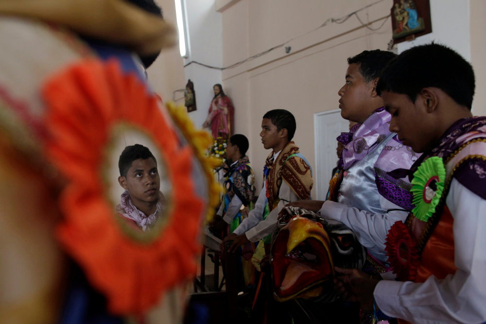 ". Youths dressed in traditional costumes as ""diablos\"" (devils) sit during the annual Corpus Christi service in La Chorrera on the outskirts of Panama City May 30, 2013. During the annual celebration, people dressed as colorful devils, angels and souls dance the \""El Baile del Gran Diablo\"" (the Great Devil Dance), representing the struggle between good and evil, in a mixture of Spanish and indigenous traditions. REUTERS/Carlos Jasso"