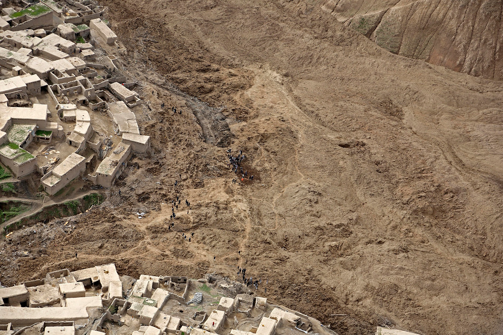 . An aerial view shows Afghans walking near the site of Friday\'s landslide that buried Abi Barik village in Badakhshan province, northeastern Afghanistan, Monday, May 5, 2014.  (AP Photo/Rahmat Gul)