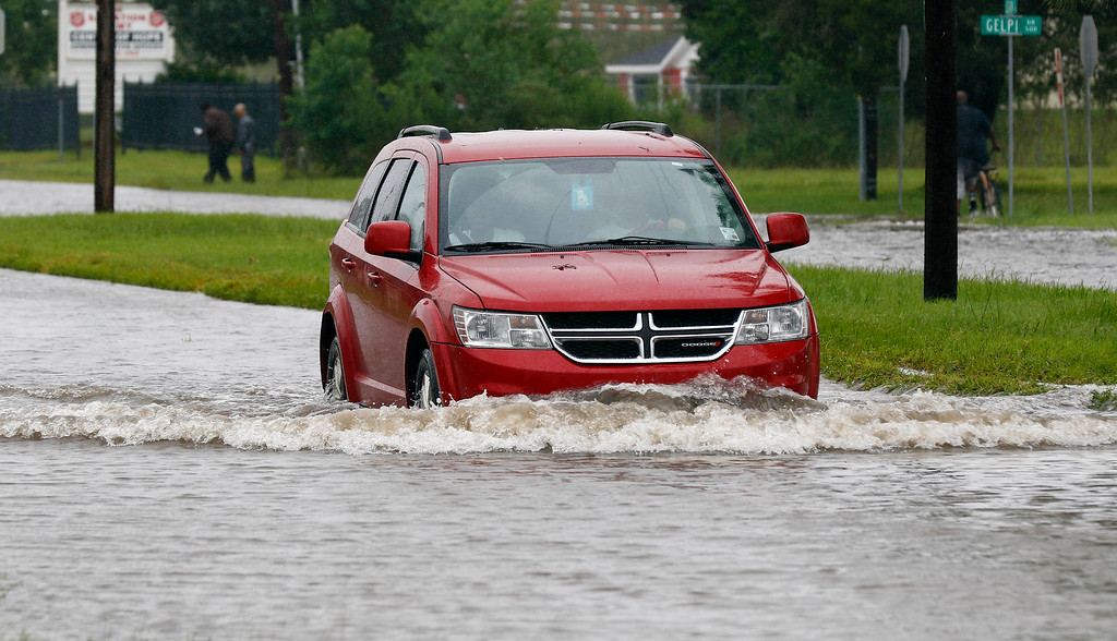 . A driver attempts to steer through the remaining floodwaters from Harvey on Legion Street in Lake Charles, La., Tuesday, Aug. 29, 2017. Many houses along Legion Street took in floodwater in part because drivers ignored the police barricades and by their driving thru caused waves that flooded the houses. (AP Photo/Rogelio V. Solis)