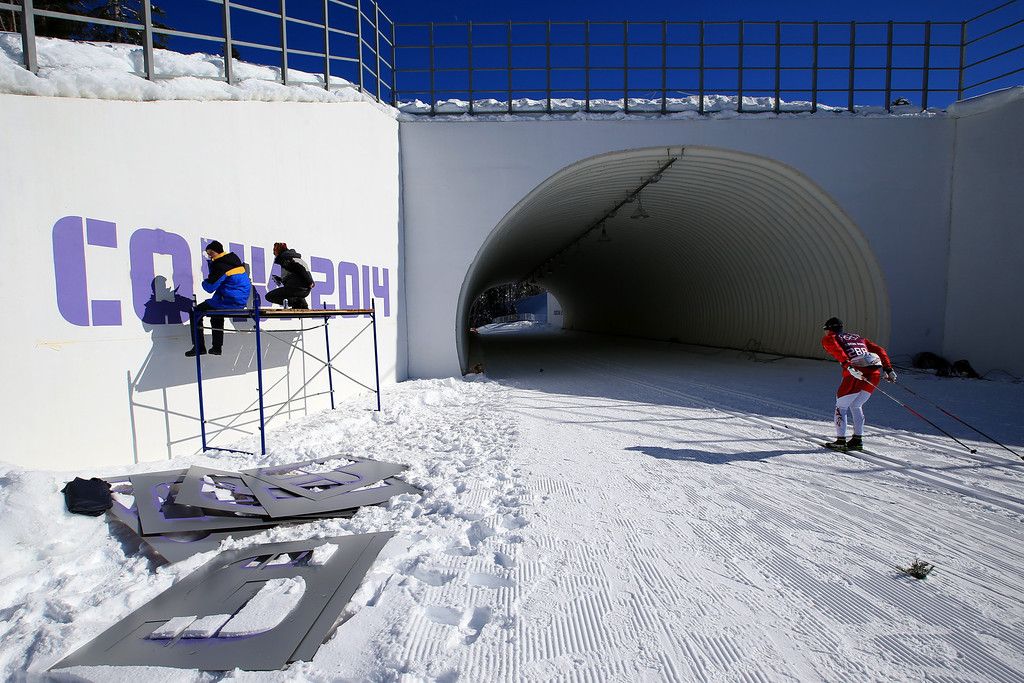 . An athlete passes workers putting the finishing touches to the course ahead of the Sochi 2014 Winter Olympics at the Laura Cross-Country Ski and Biathlon Center on February 5, 2014 in Sochi, Russia.  (Photo by Richard Heathcote/Getty Images)