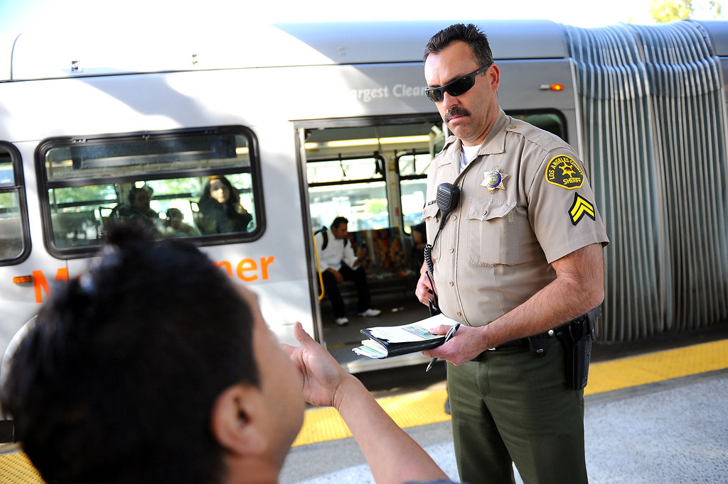 . LA County Sheriff deputy Dell Moore cites a bus rider for fare evasion during an Orange Line fare enforcement operation at the Van Nuys Orange Line Station February 25, 2014.  Officials from Metro and the Los Angeles Sheriff\'s Department Transit Services Bureau announced a new two-pronged effort to cut down on fare-evaders on the Orange Line by improving communications and beefing up enforcement.(Andy Holzman/Los Angeles Daily News)