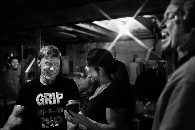 Devio and other arm wrestlers laugh at videos on fellow arm wrestler Valerie Beach's phone in Fitzsimmons' basement in West Bridgewater, Mass.