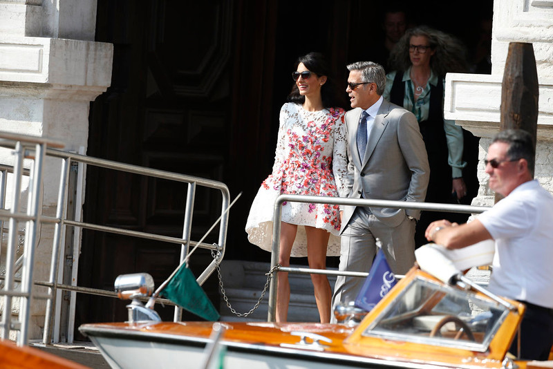 . George Clooney is flanked by his wife Amal Alamuddin as they leave the Aman luxury Hotel in Venice, Italy, Sunday, Sept. 28, 2014. George Clooney married human rights lawyer Amal Alamuddin Saturday, the actor\'s representative said, out of sight of pursuing paparazzi and adoring crowds. (AP Photo/Luca Bruno)