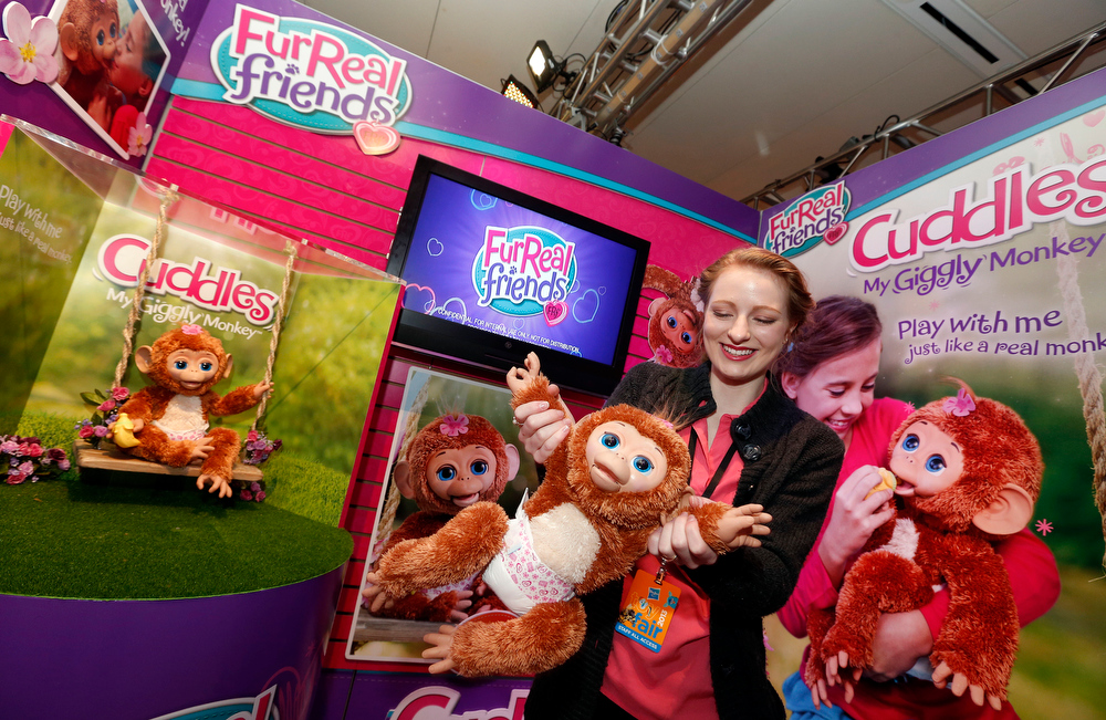Description of . FURREAL FRIENDS CUDDLES, MY GIGGLY MONKEY takes a swing with demonstrator Christa Sparks in Hasbroís showroom at the American International Toy Fair, Sunday, Feb. 10, 2013, in New York.  Available this fall at retail, Cuddles features over 100 responses making it the most interactive FURREAL FRIENDS to date. (Photo by Jason DeCrow/Invision for Hasbro/AP Images)