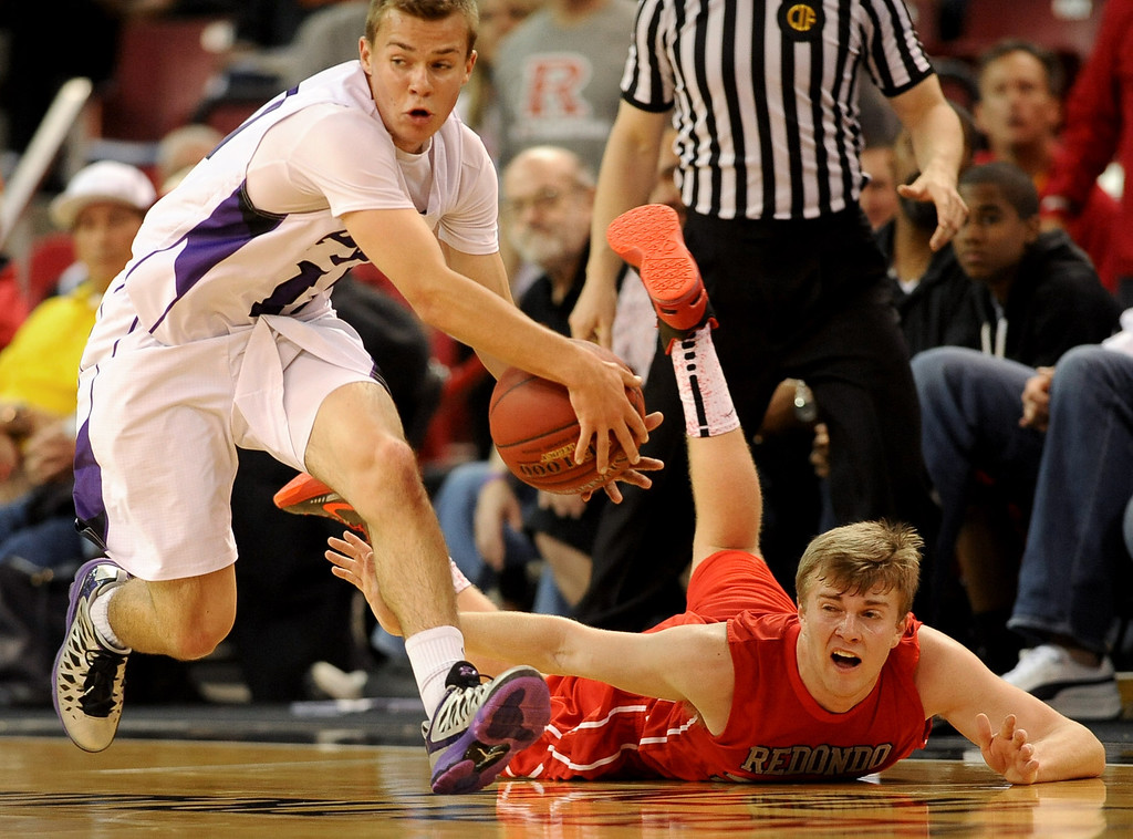 . Redondo Union High School\'s Derek Biale hits the floor while competing for a loose ball with Peter Schoemann of College Park High School during the Division II 2013 CIF State Basketball Championships at Sleep Train Arena, in Sacramento, Ca March 23, 2013.  Redondo won the game 54-47.(Andy Holzman/Los Angeles Daily News)