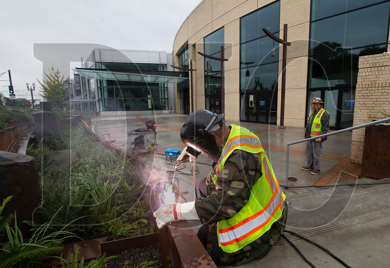 Brett Sawyer, a journeyman ironworker with Local 29 and employee of minority-owned Raimore Construction, installs skate deterrents at the the Oregon Convention Center. Raimore Construction is working on an $8.6 million subcontract for exterior work on the project. (Sam Tenney/DJC)