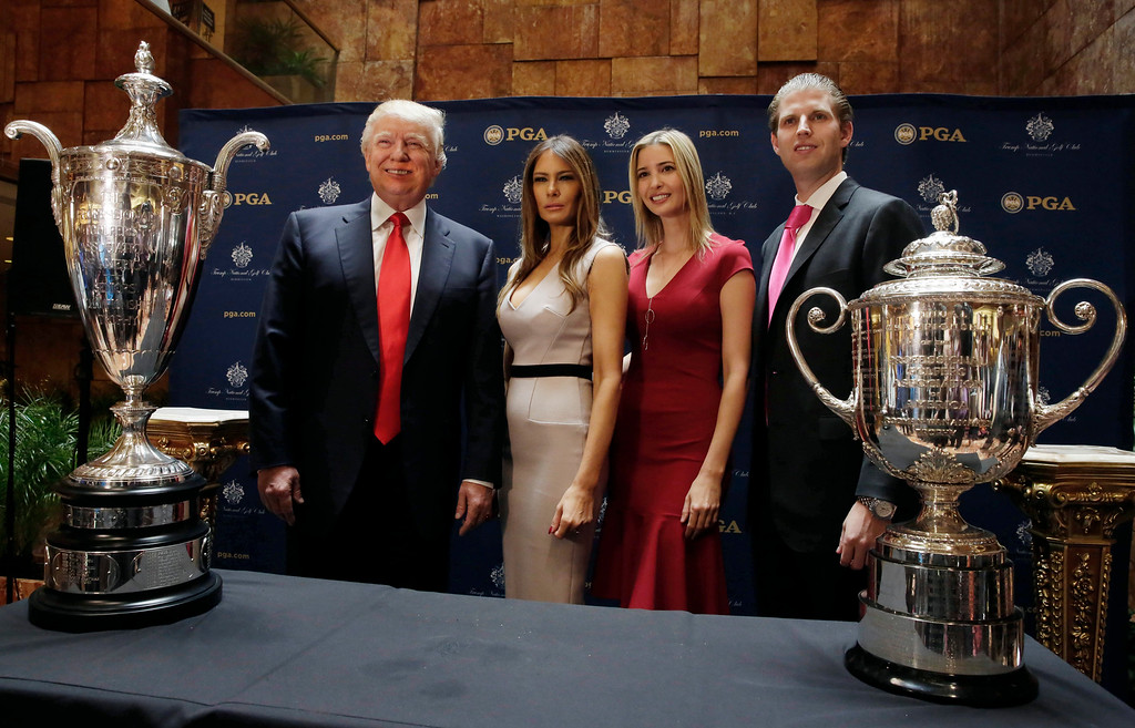 . Donald Trump, Chairman of The Trump Organization, poses for photos with his family and the PGA Senior Championship trophy, left, and the PGA Championship trophy, at a news conference, in New York, Thursday, May 1, 2014. From left are Trump, his wife Melania Trump, his daughter Ivanka Trump, and son Eric Trump. (AP Photo/Richard Drew)