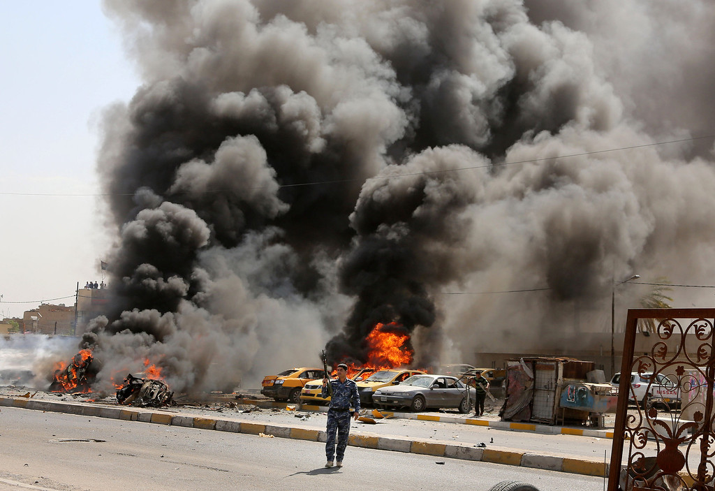 . Iraqi policemen stand near burning vehicles moments after one in a series of bombs hit the Shiite stronghold of Sadr City, in Baghdad, Iraq, Tuesday, May 13, 2014.  (AP Photo/Karim Kadim)