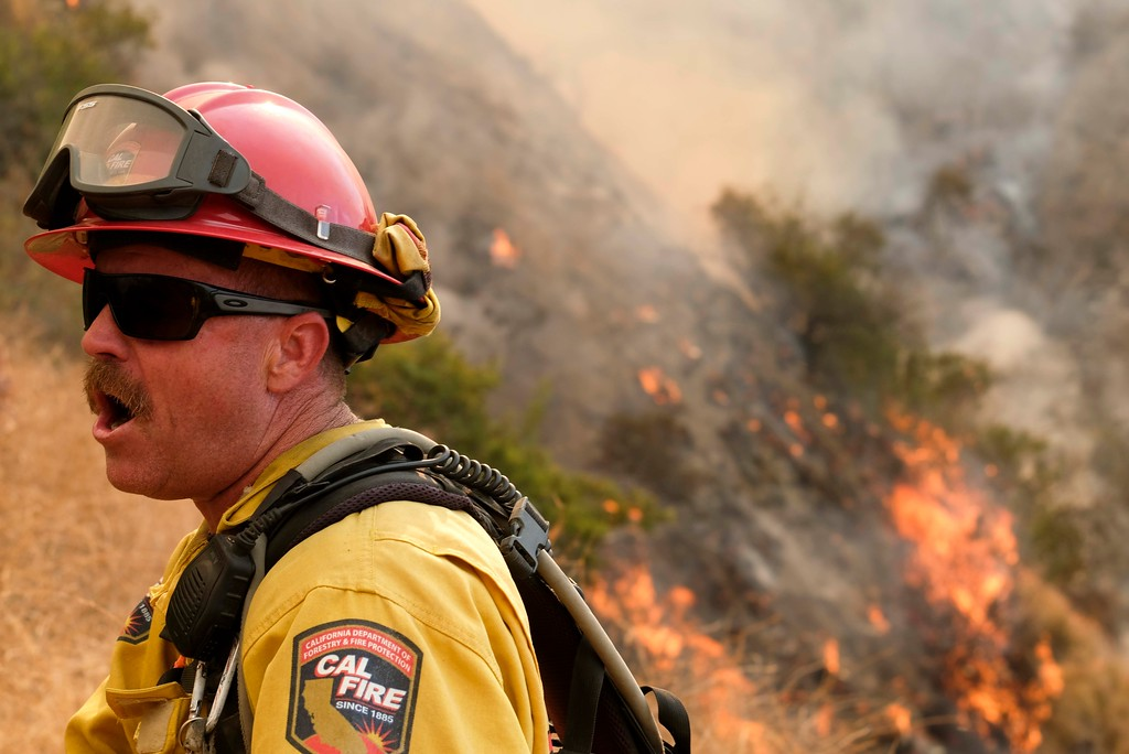 . A member with California Department of Forestry and Fire Protection (Cal Fire) battles a brushfire on the hillside in Burbank, Calif., Saturday, Sept. 2, 2017. Several hundred firefighters worked to contain a blaze that chewed through brush-covered mountains, prompting evacuation orders for homes in Los Angeles, Burbank and Glendale. (AP Photo/Ringo H.W. Chiu)