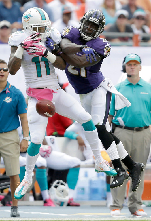 . Baltimore Ravens cornerback Lardarius Webb, right, swats away a pass intended for Miami Dolphins wide receiver Mike Wallace (11) during the first half of an NFL football game, Sunday, Oct. 6, 2013, in Miami Gardens, Fla. (AP Photo/Wilfredo Lee)