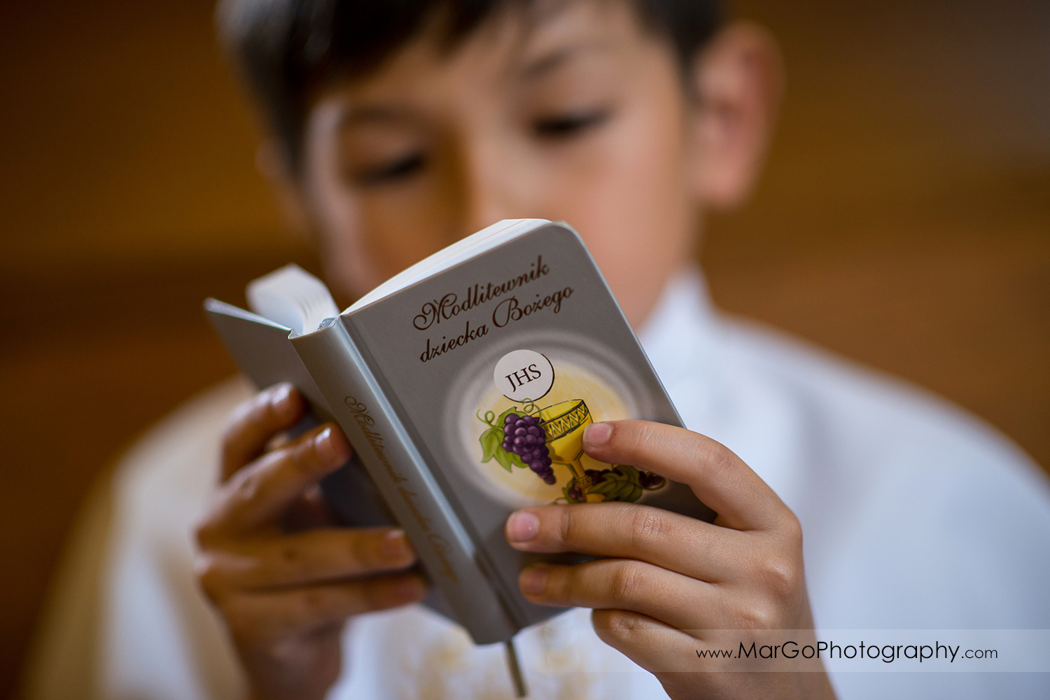 boy in white alb reading first communion book in wooden San Jose church pews