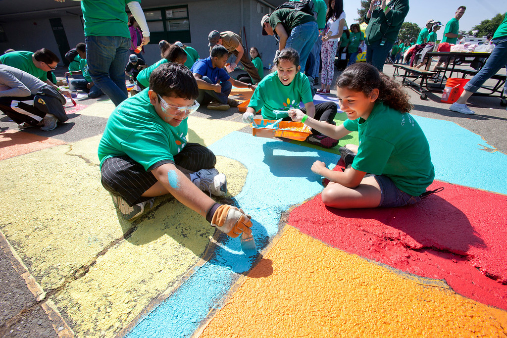 . Students, from left, Santiago Collazo, 11, Lizza Urgell, 13, and Maya Gonzalez, 13, paint a map of the U.S. on the playground as local Comcast employees and their families joined with students and parents to spend the morning planting, installing benches, painting, landscaping and cleaning up the grounds at Adelante Dual Language Academy in San Jose Saturday, April 27, 2013. The volunteer effort is part of the 12th �Comcast Cares Day,� the largest single-day corporate volunteer effort in the United States that brought together more than 70,000 Comcast employees, their families and friends nationwide to help make a difference in their communities.  3,000 Comcast employees and their families did volunteer work at 16 schools affected by budget cuts in California. (Patrick Tehan/Bay Area News Group)