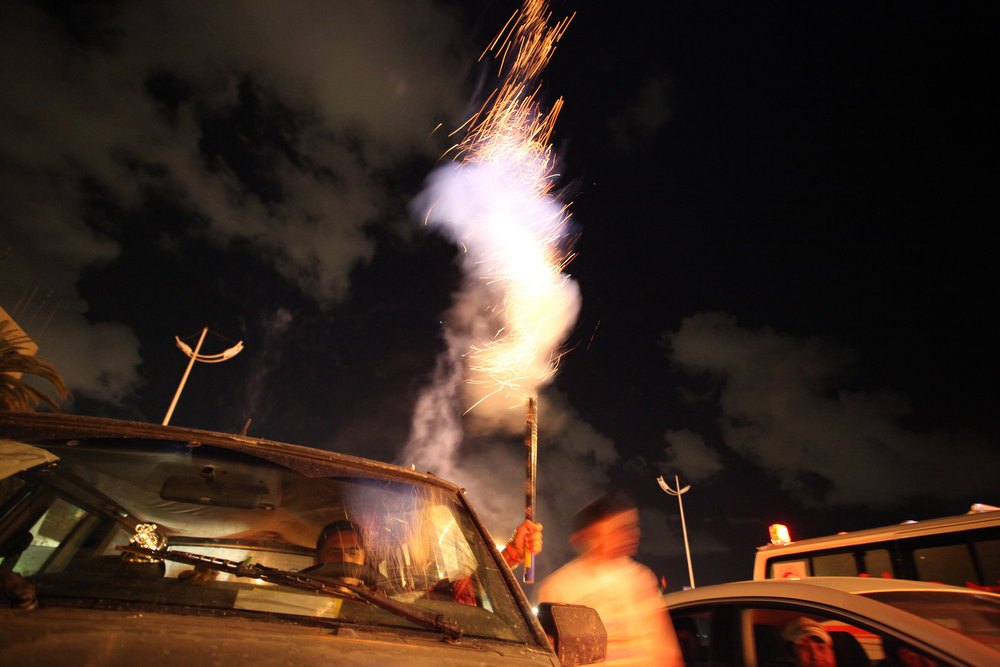 Description of . A Libyan shoots fireworks in the air during a celebration to commemorate the second anniversary of the revolution that ousted Moammar Gadhafi, in Benghazi, Libya, Friday, Feb, 15, 2013.  (AP Photo/Mohammad Hannon)