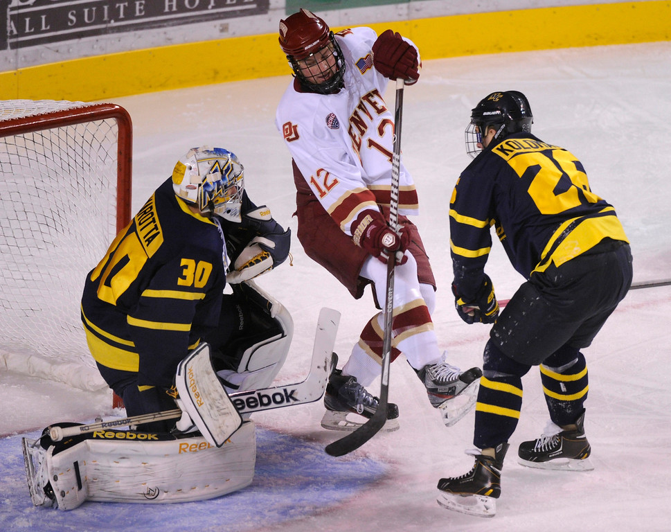 . DENVER, CO. - OCTOBER 12: Denver wing Ty Loney (12) tried to get his stick on the puck in the first period. The University of Denver hockey team hosted Merrimack at Magness Arena, Saturday night, October 12, 2013. Photo By Karl Gehring/The Denver Post