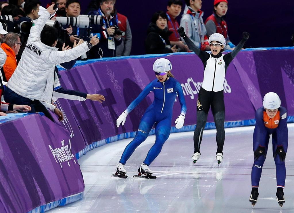 . Gold medalist Nana Takagi of Japan second right, and silver medalist Kim Bo-reum of South Korea, center in blue stop to celebrate with their coaches as bronze medalist Irene Schouten of The Netherlands passes, right, after the women\'s mass start final speedskating race at the Gangneung Oval at the 2018 Winter Olympics in Gangneung, South Korea, Saturday, Feb. 24, 2018. (AP Photo/Vadim Ghirda)