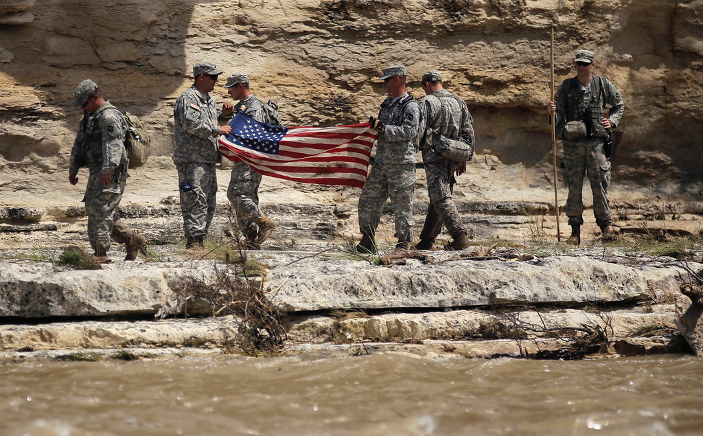 . Members of the National Guard work along the Blanco River with a search and rescue team, Tuesday, May 26, 2015, in Wimberley, Texas. Authorities say recovery teams will resume looking for as many as a dozen missing people, in an area where punishing rains have destroyed or damaged more than 1,000 homes and killed at least three people statewide this weekend. (AP Photo/Eric Gay)