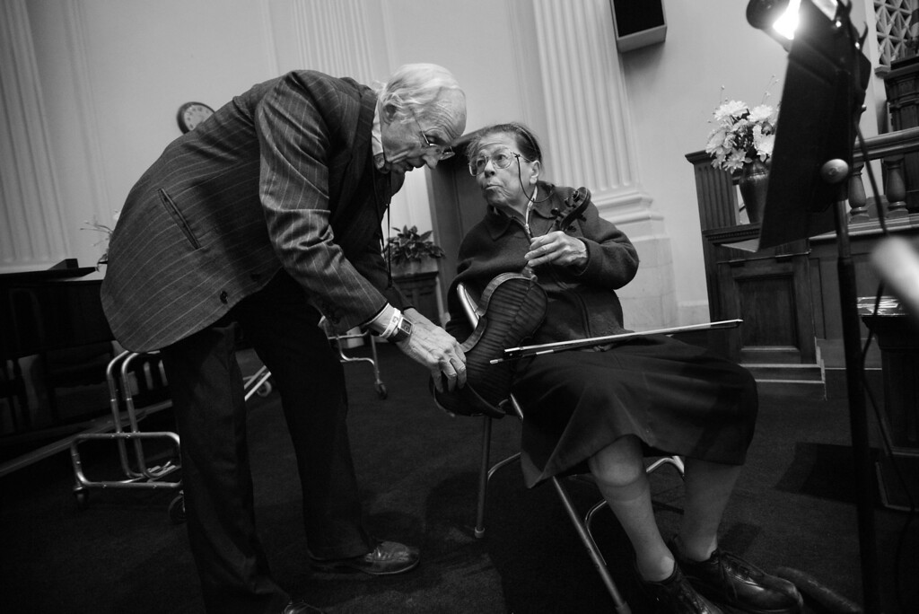 """. Second violinist Pauline Dallenbach talks with her husband Robert while preparing for a Denver Philharmonic Orchestra rehearsal at the KPOF Concert Hall in Denver, CO, Monday November 12, 2012. The couple has been involved with the orchestra since 1963 when, founder, Antonia Brico invited Pauline to play violin, \""""she had me play first violin. Well, I wasn\'t that good but she wanted me there because I was the liaison between the orchestra and the church.\"""" Pauline is the granddaughter of Alma White, founder of the Pillar of Fire Church, which invited the orchestra to play in their hall.  Pauline has been a musician most of her life, first singing on church radio station KPOF in 1928, at age two. She connects her music directly to her spirituality, \"""" It was a gift from heaven for me and continues to be... There was one time in my life when I was praying. I needed to give all I had to the Lord and my violin was my best friend. This was in 1946. I said, �it\'s not mine anymore - it\'s yours. I\'ll give it to you Lord, my violin, my best friend. I will play it... but it\'s not mine, it\'s yours.� Then he dumped a symphony orchestra in my lap,\"""" she said with a laugh.  Besides recording and broadcasting the orchestra�s performances, the couple keeps an extensive archive. Both have served on the board of directors for many years. Craig F. Walker, The Denver Post"""