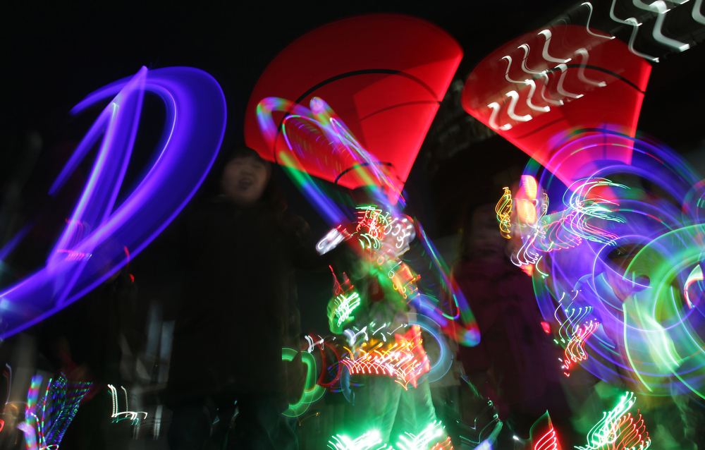 Description of . Performers spin illuminated sticks during 'Cyber Jwibulnoli' at Everland on February 21, 2013 in Seoul, South Korea. Jwibulnoli is originally played on the first full moon of the lunar year, that is February 25 this year.  (Photo by Chung Sung-Jun/Getty Images)