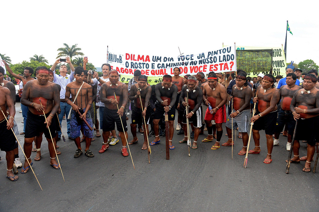 ". Indigenous people with a banner reading ""Dilma, one day you painted your face and walked by our side. Now, on what side are you?\"", dance in Brasilia on October 1, 2013, in the beginning of the National Indigenous Mobilization Week. Indigenous people from several ethnic groups will concentrate in the Brazilian capital to demand more support from the federal government during the week. AFP PHOTO / Evaristo SA/AFP/Getty Images"