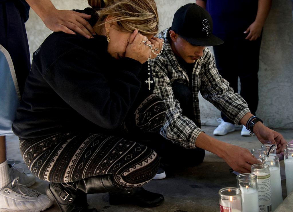 . Carmen Avila, left, mourns over the death of her son, Cristopher Rossi, 16, as friends and family gathered at the makeshift memorial outside their Duarte apartment on Tuesday, Dec. 24, 2013. Rossi was fatally shot outside his home Monday night. (Staff photo by Watchara Phomicinda/ San Gabriel Valley Tribune)